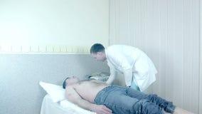 Artsen` s Handen die Elektroden voor ECG vastmaken stock videobeelden