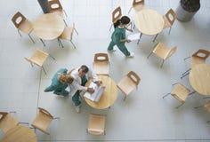 Artsen tijdens het Werkonderbreking in Cafetaria stock fotografie