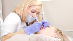 Artsencosmetologist doet de procedure van permanente make-up voor vrouwelijke cliëntlippen 4K stock videobeelden