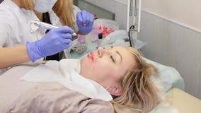 Artsencosmetologist doet de procedure van permanente make-up voor vrouwelijke cliëntlippen Langzame Motie stock videobeelden