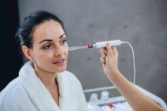 Artsencosmetologist leidt diagnostiek van een voorwaarde van een huid van het gezicht van de patiënt stock foto