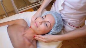 Artsencosmetologist maakt een een gezicht en neck massage Spa vrouw stock video