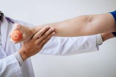 Artsenfysiotherapeut die een mannelijke patiënt bijstaan terwijl het geven uitoefenend behandeling bij het uitrekken van zijn wap royalty-vrije stock foto's