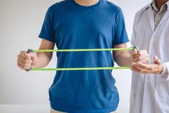 Artsenfysiotherapeut die een mannelijke patiënt bijstaan terwijl het geven uitoefenend behandeling bij het uitrekken van zijn wap stock fotografie