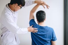 Artsenfysiotherapeut die een mannelijke pati?nt bijstaan terwijl het geven uitoefenend behandeling die de schouder van pati?nt in stock foto