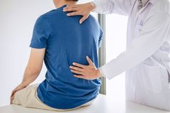 Artsenfysiotherapeut die lagere rugpijnpatiënt behandelen na terwijl het geven uitoefenend behandeling bij zich het uitrekken in  royalty-vrije stock afbeelding