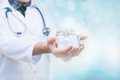 Artsenhanden die giftdoos met lint, Giften voor Patiëntenconcept houden stock afbeelding