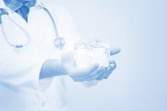 Artsenhanden die giftdoos met lint, Giften voor Patiëntenconcept houden royalty-vrije stock afbeeldingen
