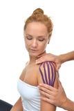 Artsenhanden die speciale fysioband op vrouwenschouder toepassen Stock Foto
