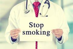 Artsenhanden die wit kaartteken met bericht van de einde het rokende tekst houden Stock Afbeelding