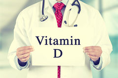 Artsenhanden die wit kaartteken met de tekstbericht van vitamined houden Stock Foto