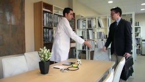 Artsenhandenschudden aan verzekeringsagent vóór vergadering stock footage