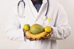 Artsenholding en het voorstellen van vruchten in handen stock foto's