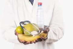 Artsenholding en het voorstellen van vruchten in handen stock foto