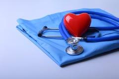 Artsenlaag met medische stethoscoop en rood hart op het bureau stock foto