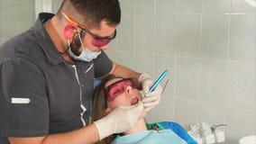 Artsenorthodontist met glazen wit de tanden van een jonge vrouw met een laser stock footage