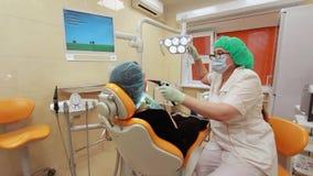Artsentandarts en meisjespatiënt in kliniek van tandheelkunde stock videobeelden