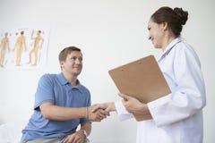 Artsenvergadering met patiënt stock afbeelding