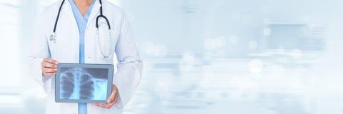 Artsenvrouw die een tablet met een radiografie houden tegen blauwe achtergrond royalty-vrije stock afbeeldingen