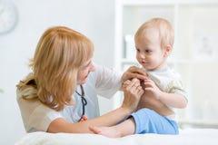 Artsenvrouw die kindjongen met stethoscoop onderzoeken Stock Fotografie