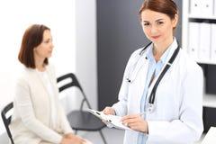 Artsenvrouw op het werk Portret die van vrouwelijke arts medische vorm opvullen terwijl status dichtbij ontvangstbureau bij klini stock foto's