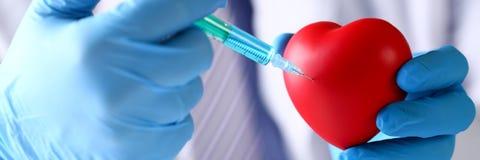Artsenwapens die de beschermende blauwe naald van de handschoenenstok dragen in hart royalty-vrije stock afbeeldingen