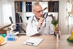 Artsenzitting bij bureau in bureau De mens bekijkt broccoli met vergrootglas stock foto