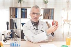 Artsenzitting bij bureau in bureau, het luisteren appel met stethoscoop royalty-vrije stock fotografie