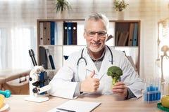 Artsenzitting bij bureau in bureau met microscoop en stethoscoop De mens geeft duimen tot broccoli royalty-vrije stock fotografie