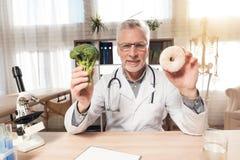 Artsenzitting bij bureau in bureau met microscoop en stethoscoop De mens houdt broccoli en doughnut stock foto's