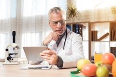 Artsenzitting bij bureau in bureau met microscoop en stethoscoop De mens houdt tablet royalty-vrije stock fotografie