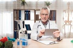 Artsenzitting bij bureau in bureau met microscoop en stethoscoop De mens houdt tablet royalty-vrije stock afbeeldingen