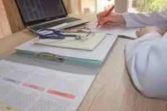 Artsenzitting bij het bureau dichtbij venster Geneeskunde arts ` s workin Stock Afbeeldingen