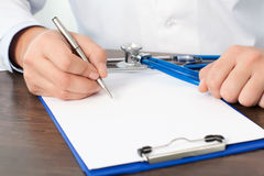 Artsenzitting bij zijn bureau met een stethoscoop en het schrijven van iets op een blad Stock Foto's