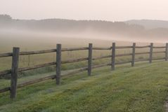 Artsy Foggy Morning Rail Fence. Western Wisconsin, foggy morning sunrise haze with trees in background, old rail fence in the front Royalty Free Stock Photography