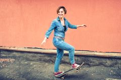 Artsy portrait of a brunette cute girl on a skateboard, laughing and having a good time. Healthy concept of modern life, hipster g Stock Image