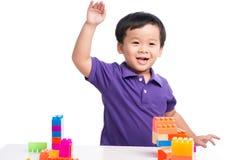 Żartuje chłopiec bawić się z blokami od zabawkarskiego konstruktora odizolowywającego Zdjęcia Stock