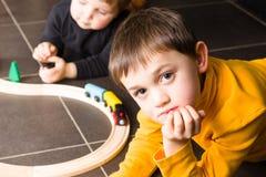 Żartuje chłopiec bawić się z drewnianymi pociągami fotografia royalty free