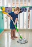 Żartuje chłopiec cleaning pokój, płuczkowa podłoga z kwaczem Mały domowy pomagier Montessori pojęcie Fotografia Stock