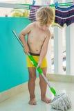 Żartuje chłopiec cleaning pokój, płuczkowa podłoga z kwaczem Mały domowy pomagier Montessori pojęcie Zdjęcia Royalty Free