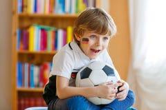 Żartuje chłopiec dopatrywania mecz futbolowego na tv lub piłkę nożną Obrazy Royalty Free