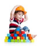 Żartuje chłopiec jako pracownik budowlany w ochronnym hełmie zdjęcia royalty free