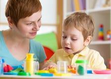Żartuje chłopiec z nauczyciel sztuki gliną, dziecinem, ośrodkiem opieki dziennej lub playschool w domu, obrazy royalty free