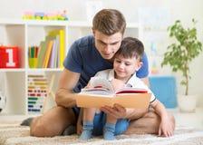 Żartuje chłopiec i ojciec czyta książkę indoors Fotografia Stock