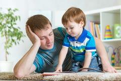 Żartuje chłopiec i ojciec czyta książkę na podłoga indoors Fotografia Stock