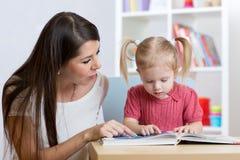 Żartuje dziewczyny i matka czyta książkę indoors Zdjęcie Royalty Free