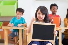 ?artuje dziewczyny mienia pustego blackboard z r??norodno?? przyjaci??mi przy t?em nauczycielem i, dziecina preschool, egzamin pr zdjęcia stock