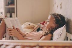 Żartuje dziewczyny obsiadanie na łóżkowej i czytelniczej książce w jej pokoju Wygodny weekend w domu obraz stock