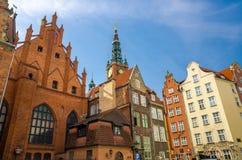 Artus Court-Backsteinbau, Fassade von schönen typischen bunten Häusern mit Rathaus-Helm und Hintergrund des blauen Himmels des Gl stockfoto
