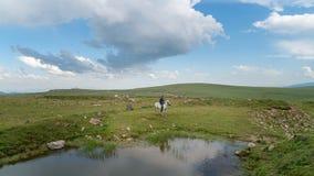 Man riding a horse inside a small pond in Savsat, Artvin, Turkey stock photo